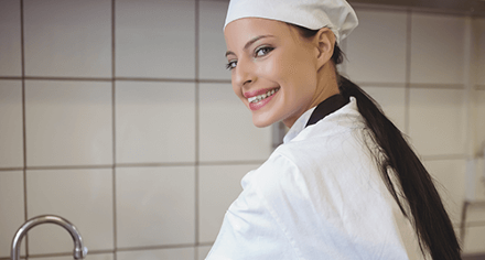 A smiling woman in a chef uniform.