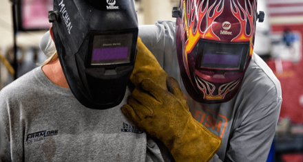 Two workers in welding helmets.